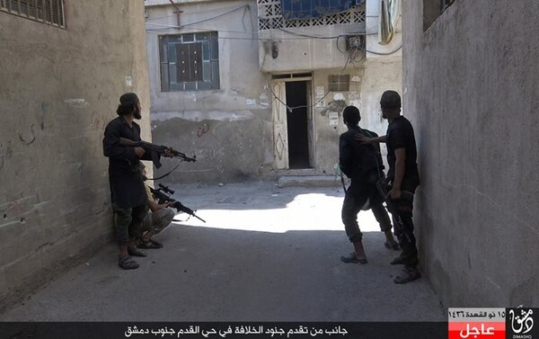 In this picture released August 30, 2015 by the Rased News Network, on a Facebook page affiliated with the Islamic State group, Islamic State militants walk on a street in the Qadam neighborhood of Damascus, Syria. Islamic State fighters on Sunday pushed into Qadam, a large district in southern Damascus, clashing with rival militants just a few kilometers from the center of the Syrian capital, the extremist group and Syrian activists said. Arabic at bottom reads,
