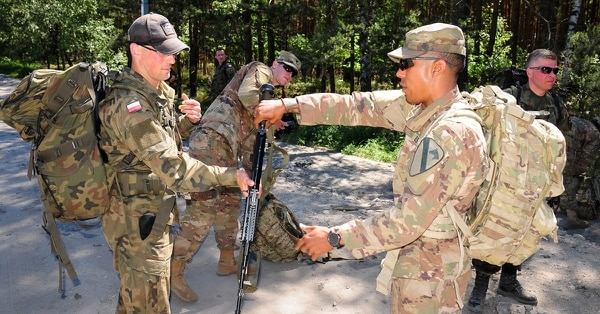 A soldier with Headquarters and Headquarters Company (HHC), 1st Armored Brigade Combat Team (1st ABCT), 1st Cavalry Division returns a rifle to a Polish soldier during a 10-kilometer ruck march in Zagan, Poland, June 7, 2018. (Sgt. 1st Class Robert Jordan/Army)