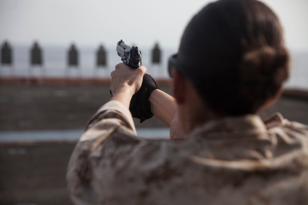 U.S. Marine Cpl. Elize McKelvey shoots at her target with an M9 Beretta pistol during a deck shoot aboard the amphibious assault ship USS Essex (LHD 2). McKelvey is a production specialist with the 15th Marine Expeditionary Unit's Command Element. These Marines executed a pistol qualification during Female Engagement Team training. The 15th MEU is embarked on the Essex Amphibious Ready Group and deployed to maintain regional security in the U.S. 5th Fleet area of operations. (U.S. Marine Corps photo by Cpl. Anna Albrecht/Released)