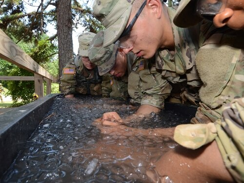 Fort Jackson basic trainees put their forearms in the tank to cool down their core temperatures after strenuous activities. The Army is researching ways to predict heat casualties before they happen.(Robert Timmons/Army)