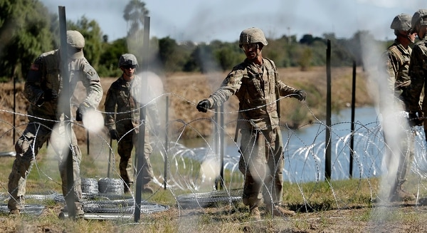 In this Nov. 16, 2018, photo, members of the U.S. military install multiple tiers of concertina wire along the banks of the Rio Grande near the Juarez-Lincoln Bridge at the U.S.-Mexico border in Laredo, Texas. The Pentagon is estimating the cost of the military's mission on the U.S.-Mexico border will be about $210 million under current plans. (Eric Gay/AP)