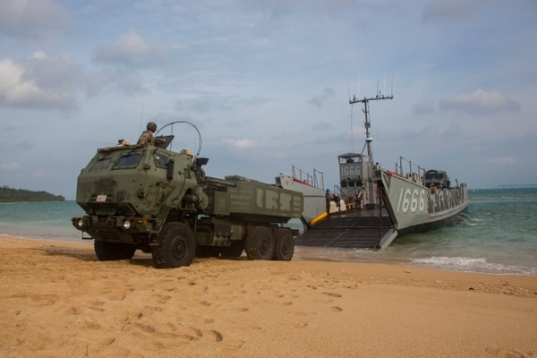 A landing craft lowers its ramp to unload a U.S. Marine Corps High Mobility Artillery Rocket System as part of a simulated amphibious raid on Okinawa in 2019. The Marines are looking to use their HIMARS system as a means of firing anti-ship missiles in the South China Sea. (Lance Cpl. Joshua Sechser/U.S. Marine Corps)