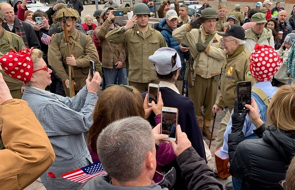 In this March 30, 2019, photo, Cpl. Clarence Smoyer, right, arrives at Union Station as volunteer historical re-enactors look on in lower downtown Denver as part of a ceremony to honor Smoyer, who served with Gen. Maurice Rose of Denver in World War II. (Kevin Simpson/The Colorado Sun via AP)