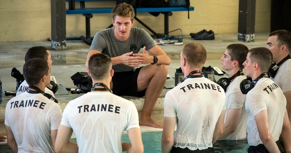 Trainees listen to the poolside instructions of an airman with the 350th Special Warfare Training Squadron. (Johnny Saldivar/Air Force)