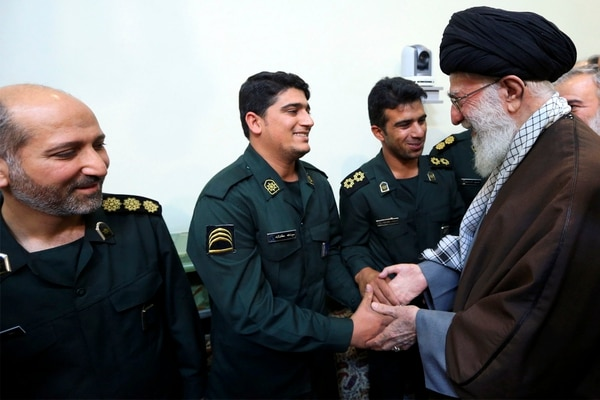 In this picture released by official website of the office of Iranian supreme leader on Sunday, Jan. 24, 2016, Supreme Leader Ayatollah Ali Khamenei greets a group of Revolutionary Guard officers who were involved in the detention of U.S. Navy sailors in Iranian water earlier this month, during their meeting in Tehran, Iran. Iran's top leader says drift of boats of U.S. Navy sailors into Iranian waters that led to their brief detention by powerful Revolutionary Guard earlier this month was a divine intervention. (Office of the Iranian Supreme Leader via AP)