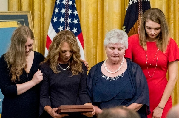 Valerie Nessel, second from left, bows her head in prayer along with her family after accepting the Medal of Honor from President Donald Trump for her husband, Air Force Tech. Sgt. John Chapman, awarded posthumously for conspicuous gallantry during a ceremony Wednesday at the White House. (Andrew Harnik/AP)
