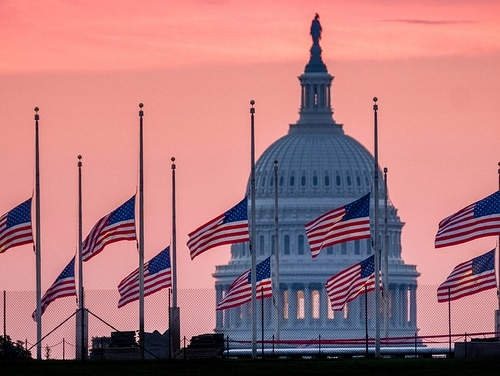 Flags flying a half-staff in honor of Sen. John McCain, R-Ariz., frame the U.S. Capital at daybreak in Washington, Sunday, Aug. 26, 2018. McCain, 81, died at his ranch in Arizona after a yearlong battle with brain cancer. (J. David Ake/AP)
