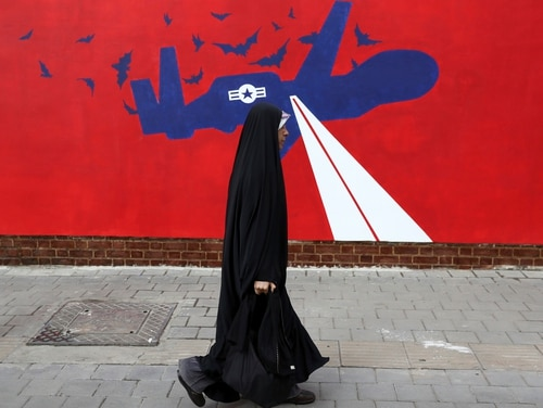 A woman walks past a new anti-U.S. mural on the wall of former U.S. Embassy portraying the interception of an American Global Hawk drone by Iran in Persian Gulf, after an unveiling ceremony in Tehran, Iran, Saturday, Nov. 2, 2019. (Vahid Salemi/AP)