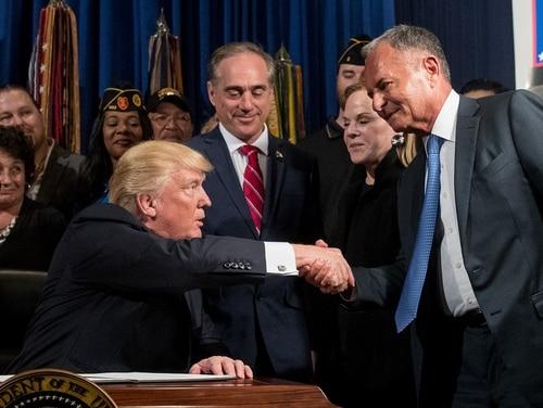 President Donald Trump, left, accompanied by then Veterans Affairs Secretary David Shulkin, center, shakes hands with Isaac