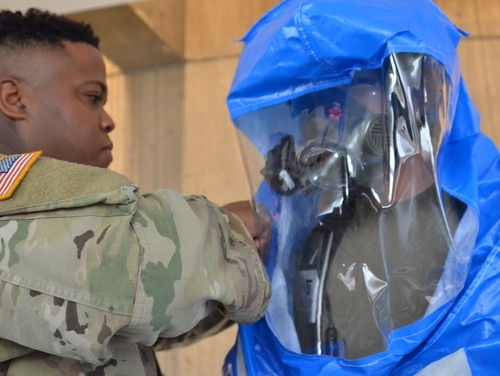 A CBRN soldier with the Michigan National Guard's 46th Military Police Command suits up a fellow soldier during training for a potential nuclear attack on Detroit, Michigan. (Army)