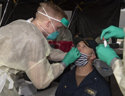 Hospital Corpsman Ethan Holder, left, takes a test sample from Cmdr. Andrew Koy, commanding officer of the guided-missile destroyer Sterett, during COVID-19 testing in April 2020. (Navy)