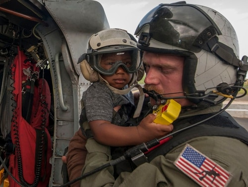 Naval Aircrewman (Helicopter) 2nd Class Brandon Larnard, from Helicopter Sea Combat Squadron 22, carries an evacuee in the wake of Hurricane Maria on the island of Dominica in 2017. The Navy recently did away with a task force dedicated to the effects of climate change, reversing an initiative by the Obama administration. (Mass Communication Specialist 3rd Class Sean Galbreath/Navy)