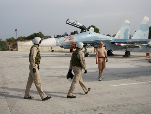Russian pilots walk to their Su-30 jet at Hemeimeem airbase, Syria, on Oct. 22, 2015. (AP Photo/Vladimir Isachenkov)