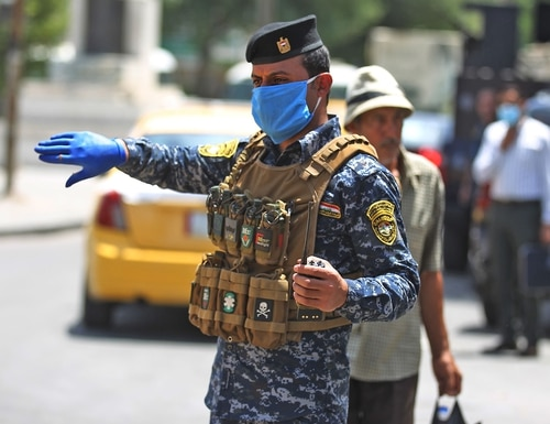 Members of the Iraqi security forces wearing protective masks keep watch at Tahrir Square in central Baghdad on May 14, 2020, during the Muslim holy month of Ramadan after authorities eased up the lockdown measures that they had imposed in a bid to slow the spread of the novel coronavirus. (Ahmad al-Rubaye/AFP via Getty Images)