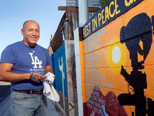 Marine veteran Cesar Lopez poses by a mural on a wall outside his home in Las Vegas, Wednesday, Aug. 12, 2020. (Steve Marcus/Las Vegas Sun via AP)