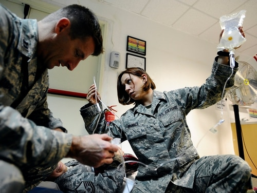 Capt. John Davis, a clinical nurse, troubleshoots an intravenous pump as Senior Airman Samantha Brunner, an aerospace medical service journeyman, inspects the IV pump's port for any kind of blockage November 2008 at Joint Base Balad, Iraq. The airmen were preparing patients for an aeromedical evacuation flight. The Air Force is now accepting applications from enlisted airmen who want to become nurses and earn their commissions. (Airman 1st Class Jason Epley/Air Force)