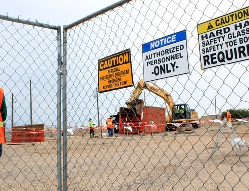 A contract employee watches crews excavate contaminated soil at Kirtland Air Force Base, N. Mex., in August 2014. Millions of gallons of jet fuel leaked underground over decades. A coalition of state lawmakers and nonprofit groups took the first step Friday toward suing the Air Force, saying it wants firm deadlines for cleaning up the contamination. (Susan Montoya Bryan/AP)