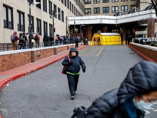 A woman walks past a line of workers and visitors waiting to be tested for coronavirus at the main entrance to a New York City Veterans Affairs hospital on March 23, 2020. (John Minchillo/AP)