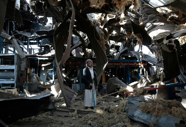 In this Sept. 22, 2016, file photo, a man stands among the rubble of the Alsonidar Group's water pump and pipe factory after it was hit by Saudi-led airstrikes in Sanaa, Yemen. (Hani Mohammed/AP)