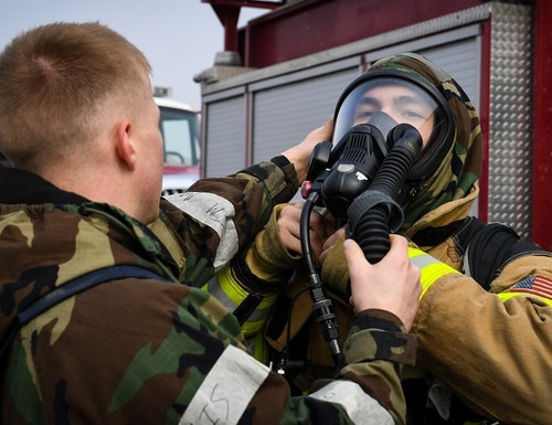 Firefighters from the 51st Civil Engineer Squadron assist each other in donning their protective equipment at Osan Air Base, Republic of Korea, on March 26, U.S. and Republic of Korea Air Force airmen will continue to train together to improve communications and interoperability. (Staff Sgt. Benjamin Raughton/Air Force)