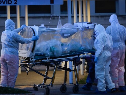 A patient in a bio-containment unit is carried on a stretcher at the Columbus Covid 2 Hospital in Rome. Italian health authorities are toiling to contain the pandemic. (Alessandra Tarantino/AP)