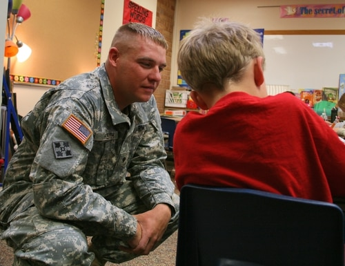 Spc. Bryan Keith, fire detection control specialist, Battery B, 3rd Battalion, 16th Field Artillery Regiment, 2nd Brigade Combat Team, 4th Infantry Division, helps a child with his reading work at Keller Elementary School Sept. 25, 2012.