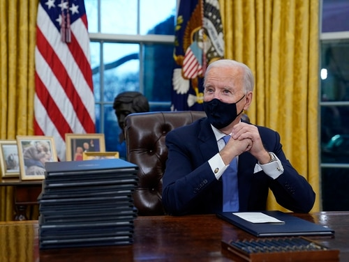 President Joe Biden waits to sign his first executive order in the Oval Office of the White House on Wednesday, Jan. 20, 2021, in Washington.(Evan Vucci/AP)