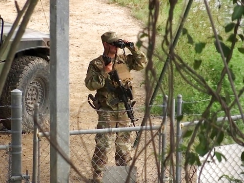 In this April 10, 2018, frame from video, a National Guard troop watches over the Rio Grande River on the border in Roma, Texas. The deployment of National Guard members to the U.S.-Mexico border at President Donald Trump's request was underway Tuesday with a gradual ramp-up of troops under orders to help curb illegal immigration. (John Mone/AP)
