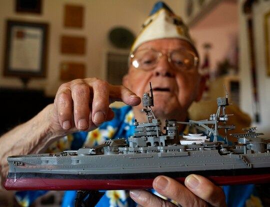 Mickey Ganitch holds up a model of the USS Pennsylvania and points to where he served as a lookout during the 1941 attack on Pearl Harbor, in the living room of his home in San Leandro, Calif., Nov. 20, 2020. (Eric Risberg/AP)
