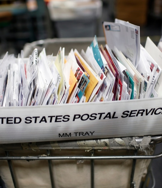The Postal Service adheres to CDC guidelines and provides masks to all employees, a USPS spokesman said. Stephen Lam/Getty Images)