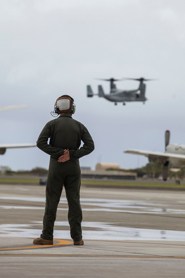 A Marine stands by to guide MV-22B Ospreys assigned to Marine Medium Tiltrotor Squadron 363 (VMM-363) that are arriving on Marine Corps Air Station Kaneohe Bay, Marine Corps Base Hawaii, July 7. (Sgt. Jesus Sepulveda Torres/Marine Corps)
