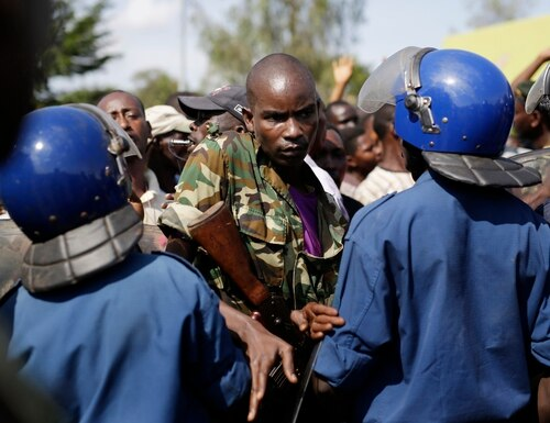 A soldier breaks through a police blockade as protesters march through the Musaga district of Bujumbura, in Burundi, Monday, May 11, 2015. Police and army negotiated with over 2000 protesters to allow delivery trucks to enter the city. One person was killed in a clash with Burundi's police on Sunday in demonstrations in the capital, Bujumbura, as the government ordered a ban on any further street protests over President Pierre Nkurunziza's bid for a third term in power. (AP Photo/Jerome Delay)