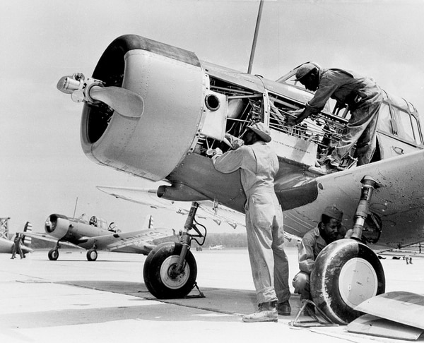 African-American airplane mechanics of the 99th Pursuit Squadron inspect the engine of a BT-13 Valiant trainer aircraft at the new U.S. Army Flying School in Tuskegee, Ala., Sept. 5, 1942. (AP Photo)