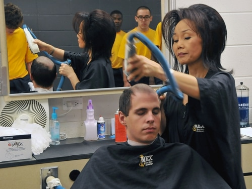 Hyong Davis gives a new recruit his first haircut in the Golden 13 Recruit In-processing Center Navy Exchange barber shop at Recruit Training Command (RTC) during Night of Arrival.(Scott A. Thornbloom/Navy)