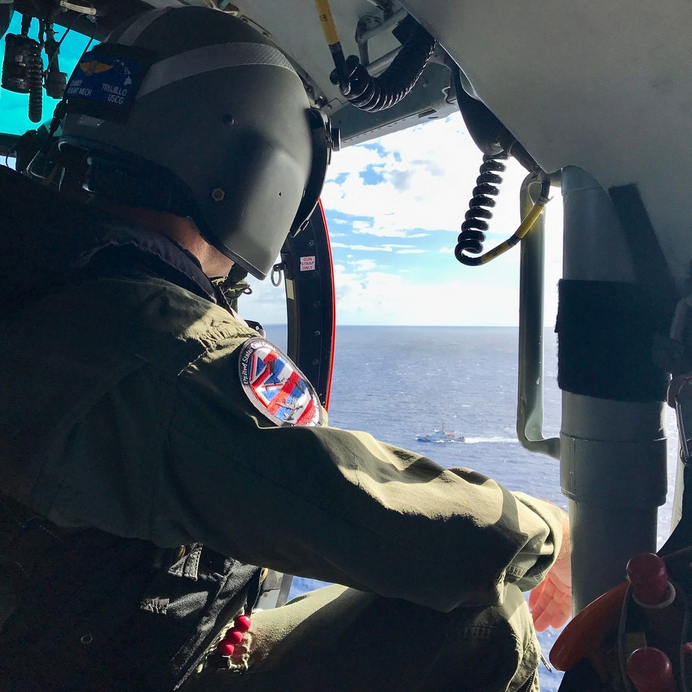 An aircrewman aboard a Coast Guard MH-65 Dolphin helicopter from Air Station Barbers Point scans the waters off Oahu Aug. 18, 2017, for any sign of five missing aviators from an Army UH-60 Black Hawk helicopter. (Coast Guard photo by Air Station Barbers Point)