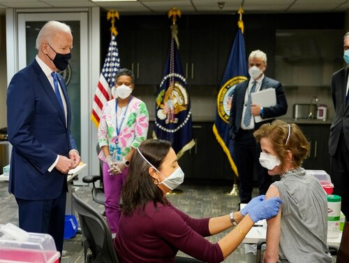 President Joe Biden, left, visits a COVID-19 vaccination site at the Washington, D.C., VA Medical Center and watches as Dr. Navjit Goraya gives a vaccine to Air Force Col. Margaret Cope on March 8, 2021. White House COVID-19 Response Coordinator Jeff Zients, standing center, and Veterans Affairs Secretary Denis McDonough, right, also attended the event. (Patrick Semansky/AP)