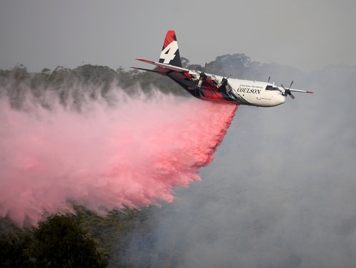 In this Jan. 10, 2020, photo, Rural Fire Service large air tanker 134, operated by Coulson Aviation in the U.S. state of Oregon, drops fire retardant on a wildfire burning close to homes at Penrose, Australia, 165km south of Sydney. Three American crew members died Thursday when this C-130 Hercules aerial water tanker crashed while battling wildfires in southeastern Australia, officials said. (Dan Himbrechts/AAP Image via AP)