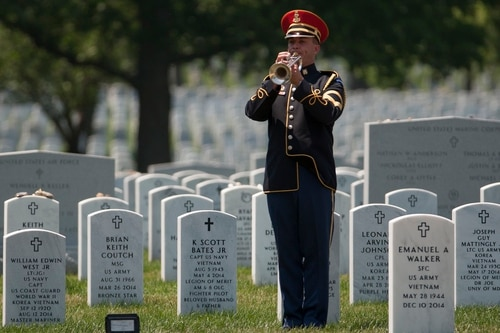 A bugler from the U.S. Army Band plays Taps during a burial service at Arlington National Cemetery in Arlington, Va. (Mike Morones/Military Times)