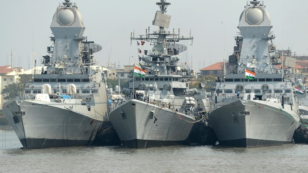 Indian naval sailors on a rubber inflatable boat pass naval warships at the Naval Dockyard in Mumbai on April 20, 2015. (Indranil Mukherjee/AFP via Getty Images)