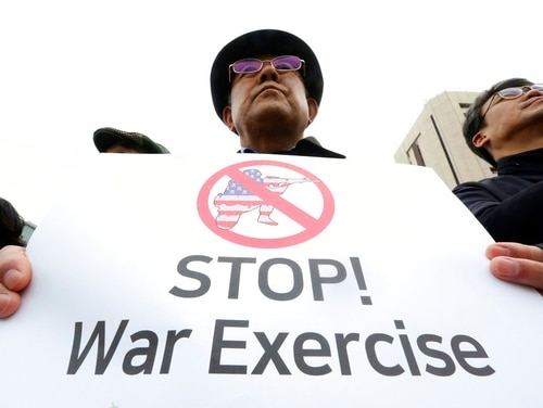 A protester holds a sign to denounce the planned annual joint military exercises between South Korea and the United States, during a rally near the U.S. Embassy in Seoul, South Korea, Wednesday, March 21, 2018. (Ahn Young-joon/AP)
