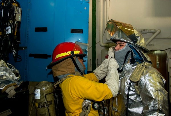 150506-N-FY142-018 PORTSMOUTH, Va. (May 6, 2015) Aviation Boatswain's Mate (Handling) 3rd Class T. A. Taifai, left, helps Aviation Boatswain's Mate (Handling) Airman M. E. Rojero don firefighting gear during a general quarters drill aboard aircraft carrier USS Harry S. Truman (CVN 75). GQ drills prepare Sailors to be at the highest state of readiness in the event of an emergency. Truman is currently undergoing a condensed incremental availability period at Norfolk Naval Shipyard while training and acquiring certifications required for its upcoming deployment. (U.S. Navy photo by Mass Communication Specialist Seaman Apprentice A. L. M. VanGuilder/Released)