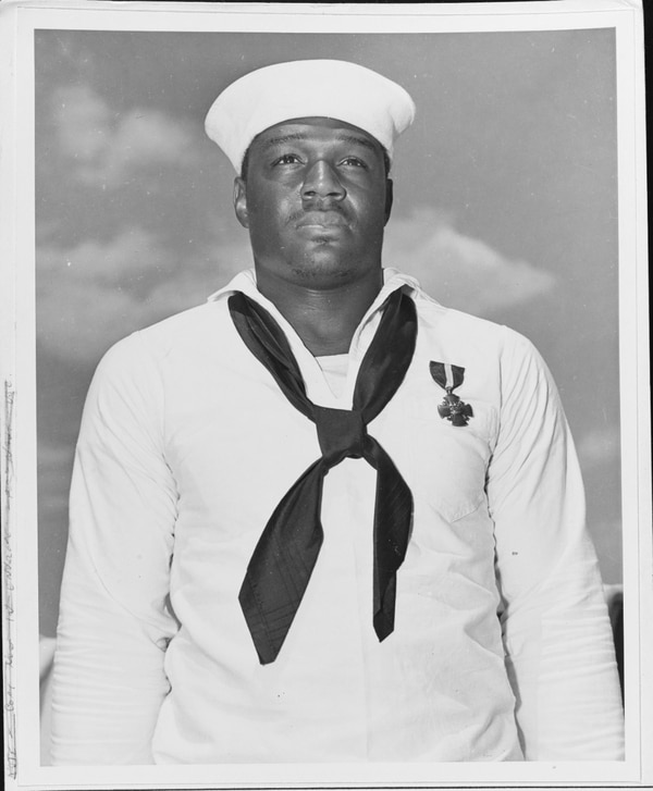 Mess Attendant 2nd Class Doris Miller (1919-1943), shortly after being presented with the Navy Cross by Adm. Chester W. Nimitz, on board the aircraft carrier Enterprise at Pearl Harbor, 27 May 1942. (National Archives)