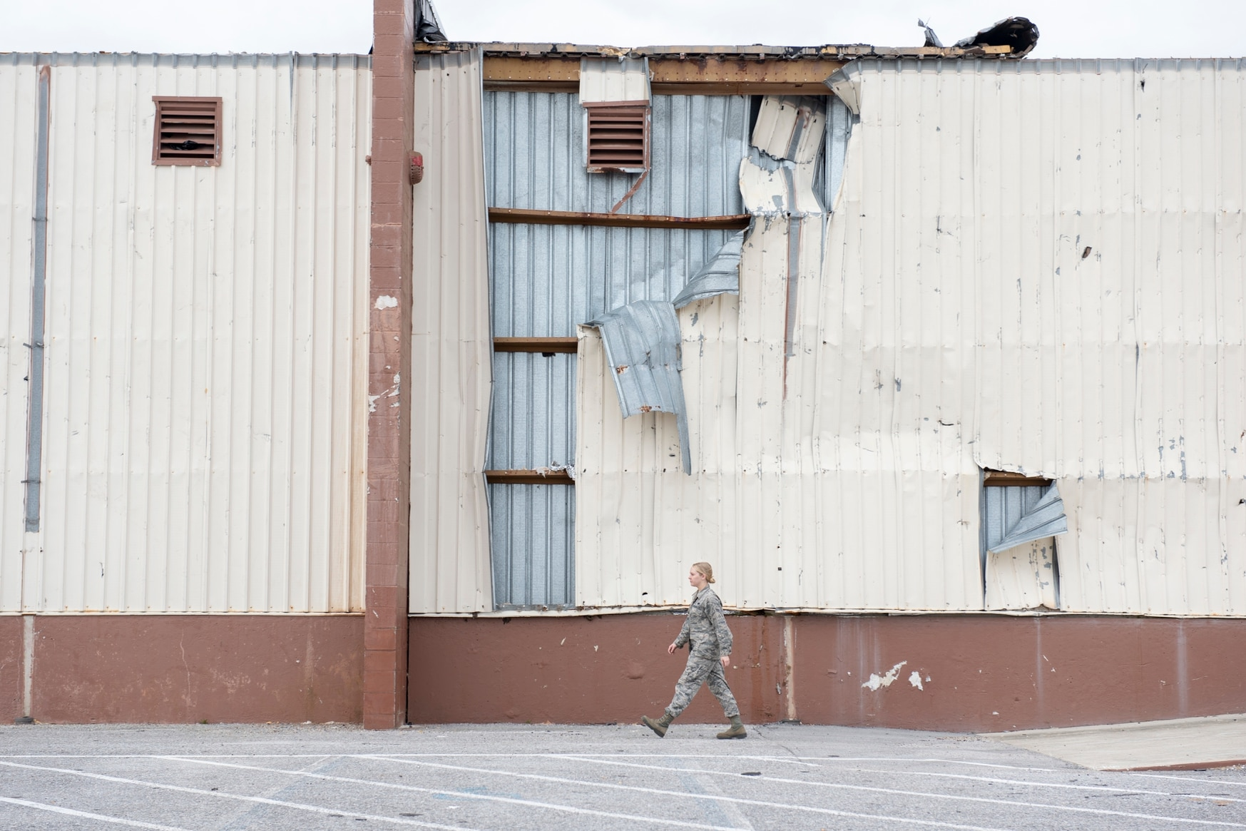 An airman walks past the 325th Logistics Readiness Squadron materiel management flight warehouse at Tyndall Air Force Base, Fla., in 2019. Airmen from various installations traveled there in support of post Hurricane Michael recovery efforts. (Senior Airman Javier Alvarez/U.S. Air Force)