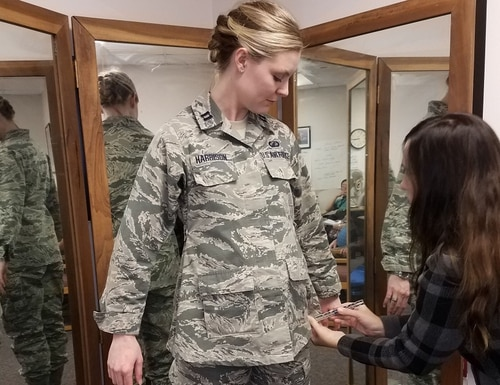 The Air Force is looking for female airmen to take part in a survey regarding their satisfaction with maternity uniform items. Here, Stacey Butler, a clothing designer with the Air Force Uniform Office, measures Capt. Taylor Harrison's maternity ABU in December 2017. (Brian Brackens/Air Force)
