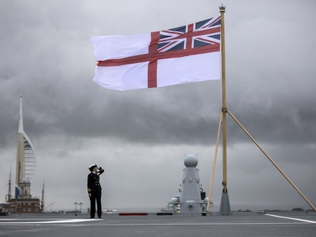 A naval officer looks up at the fluttering White Ensign flag hoisted at the stern during the commissioning ceremony for the Royal Navy's aircraft carrier HMS Queen Elizabeth (Richard Pohle/AFP via Getty Images)