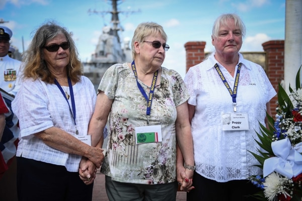 Widows of the submarine Scorpion's crew hold hands during a memorial ceremony for the 50th anniversary of the disaster last year. Held at the Scorpion Memorial on Naval Station Norfolk, the ceremony was attended by more than 500 family members, friends and shipmates of the 99 crew members lost in 1968. (Mass Communication Specialist 3rd Class Colbey Livingston/Navy)