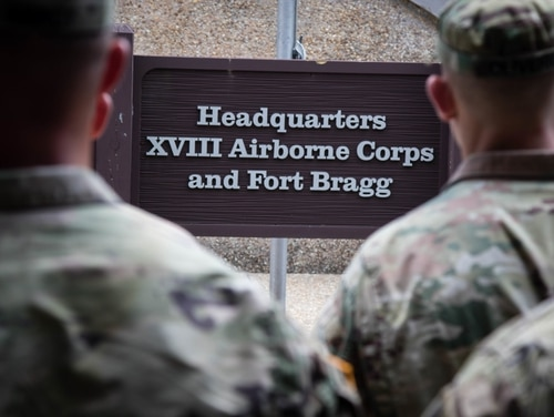 Soldiers stand before the XVIII Airborne Corps Headquarters sign at Fort Bragg, N.C., on June 28, 2019. President Donald Trump said Wednesday that he would not support efforts to rename the military base, which honors a Confederate general. (Pfc. Joshua Cowden/Army)