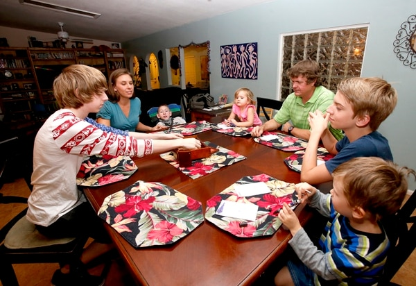 In this Wednesday, Sept. 30, 2015 photo, from left, Jo Armstrong, Julie Armstrong, Skylar Armstrong, Amelia Anderson, Nathan Anderson, Westley Armstrong and Dean Anderson sit together for a game at their home in Tucson, Ariz. At 42 with a blended family of five, Nathan Anderson runs an acupuncture clinic with his wife, Julie, also an acupuncturist. Combined, their monthly student loans bills approach $1,700.