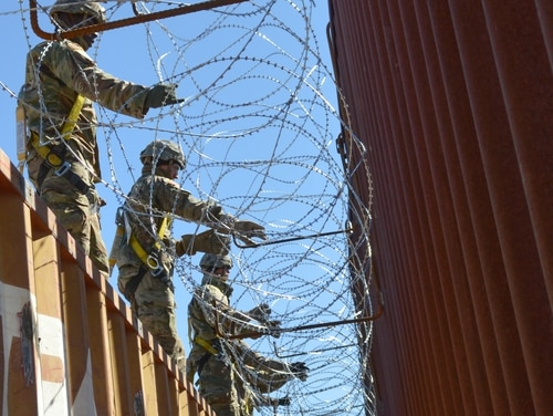 Soldiers assigned to 515th Engineer Company and 65th Military Police Company place concertina wire on a border wall in Sasabe, Ariz., on Feb. 7, 2019. (Sgt. 1st Class TaWanna Starks/Army)