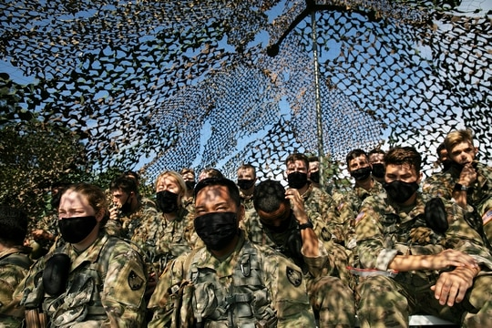Cadets wear masks as they sit under camouflage netting, Friday, Aug. 7, 2020, in West Point, N.Y. (Mark Lennihan/AP)